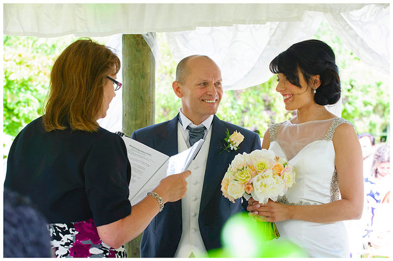 smiling bride and groom during exchanging vows