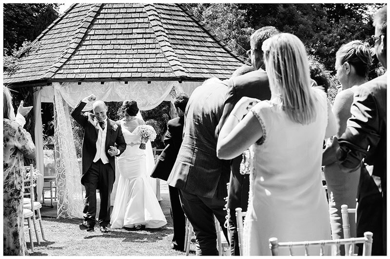 groom punches air as he leaves gazebo after outdoor ceremony in chippenham park gardens