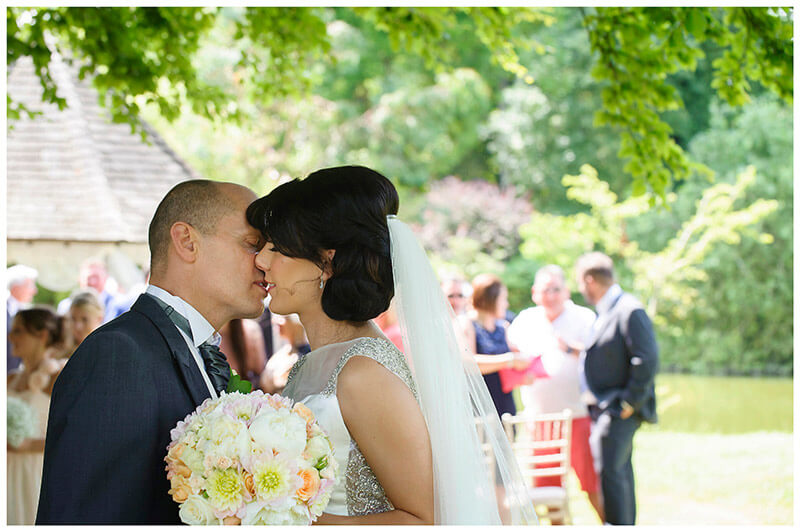 groom kisses bride after ceremony