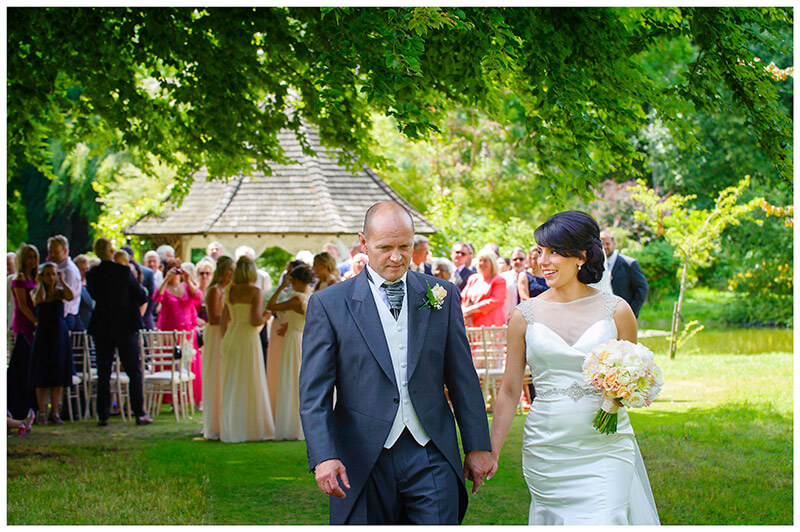 smiling bride and groom leave wedding ceremony in chippenham park gardens