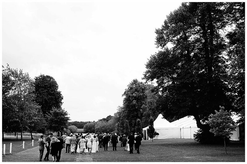 guests walking to marquee near lake at chippenham park wedding