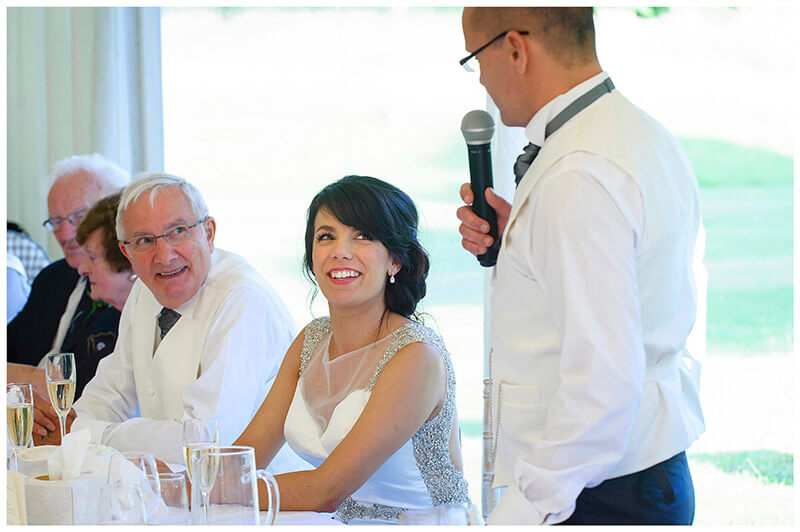 bride smiling at groom during his speech
