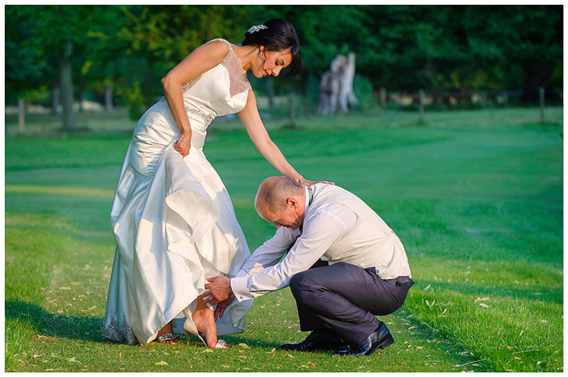 groom helps bride with shoes in chippenham park grounds