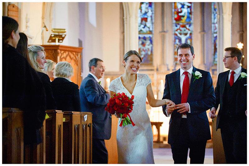 documentary wedding photographer bride groom smiling walking down aisle