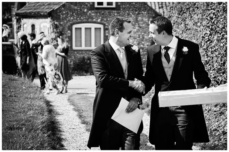 groom best man shake hands walking to church documentary wedding photographer