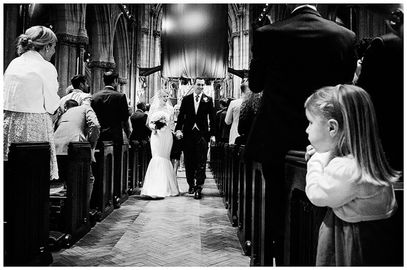 bride groom watched by young girl walking down aisle documentary wedding photographer