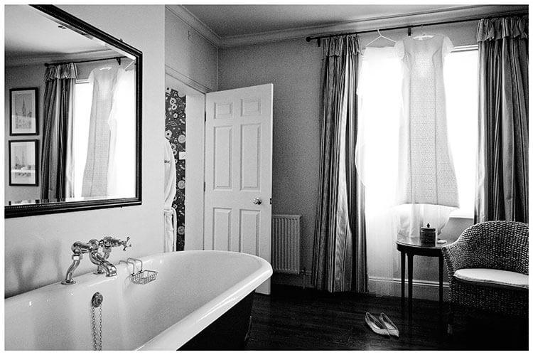 Old Bridge Hotel Wedding dress hanging on curtain rail in Bathroom