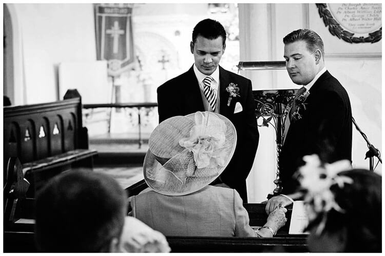 Hartford Church Wedding groom usher talking to grooms mother touches grooms hand