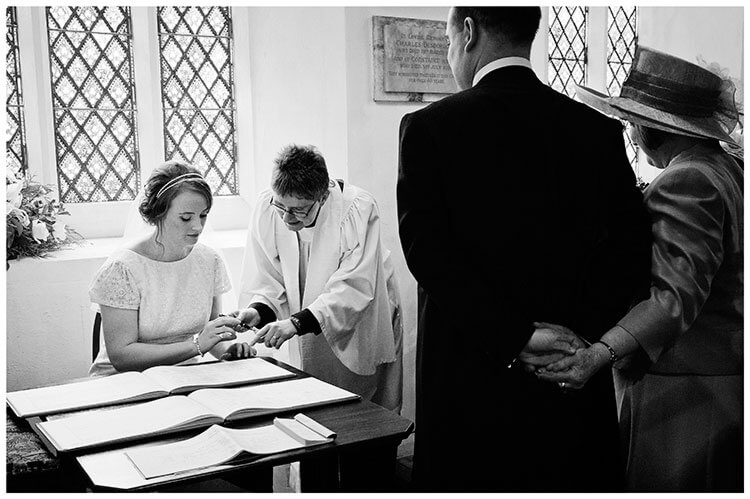 Hartford Church Wedding bride signs register watched by groom and his mother