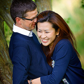 happy couple hug leaning against a tree during pre-wedding-photography-hengrave-hall