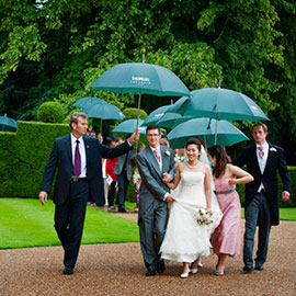 wedding photography hengrave hall roger hanako bridal party take cover under umbrellas as they walk to the reception