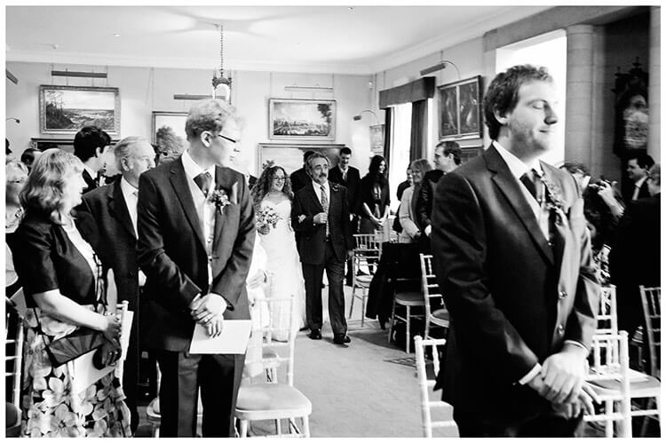 Anglesey Abbey wedding groom eyes closed as bride arrives