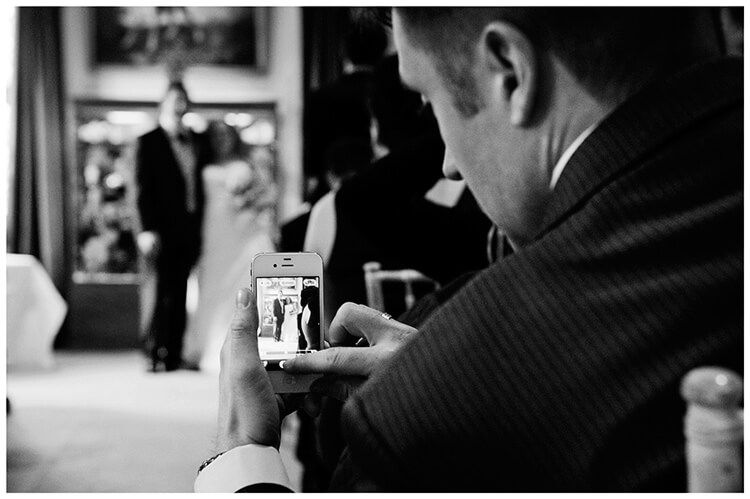 Anglesey Abbey wedding guest taking photo on phone