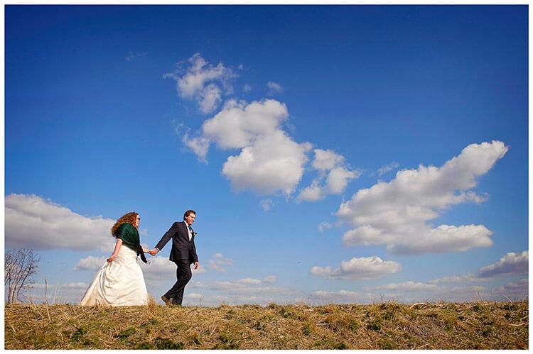 Anglesey Abbey wedding bride groom walking blue sky