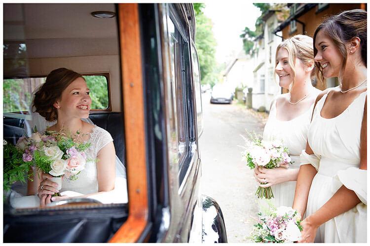 Hemingford Grey wedding smiling bride in wedding car bridesmaids