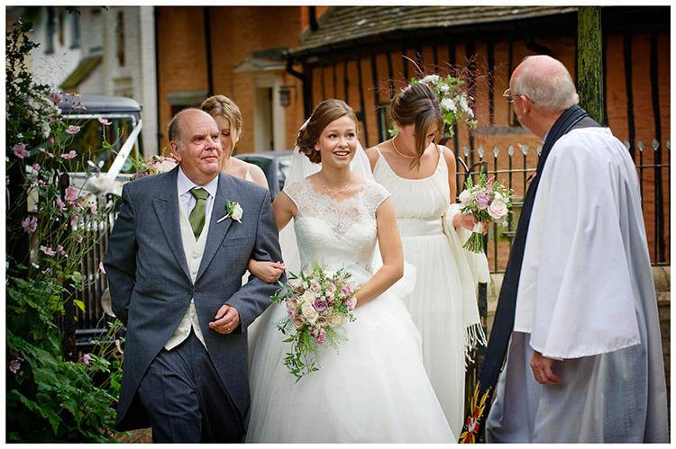 Hemingford Grey wedding bridal party greeted by vicar at church gate