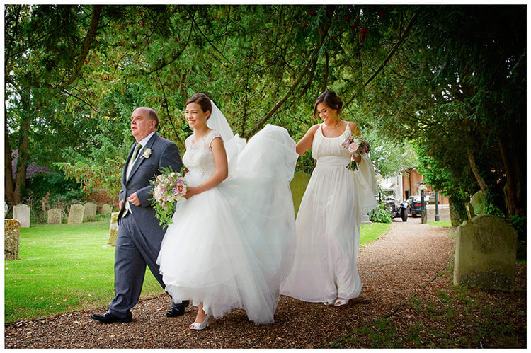 Hemingford Grey wedding brides maid holds up dress as bride walks along path on fathers arm