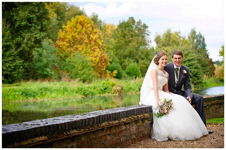 Hemingford Grey wedding bride groom sitting on wall nest to river