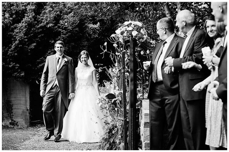Hemingford Grey wedding bride groom walking towards guests for confetti throwing