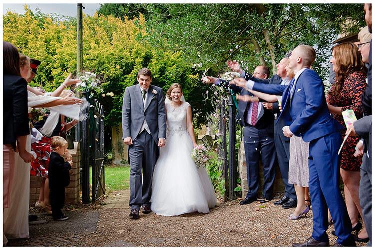 Hemingford Grey wedding smiling bride groom confetti