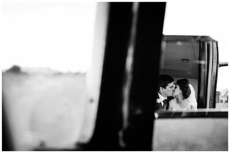 belfry hotel wedding bride groom kiss rear view mirror reflection