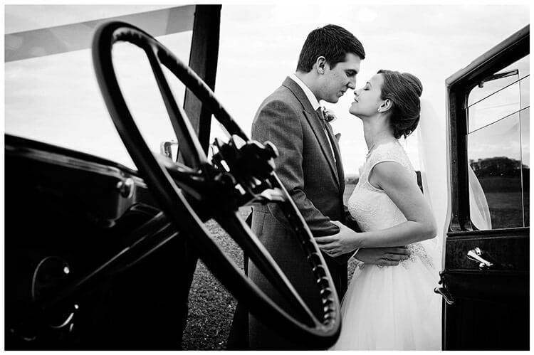 belfry hotel wedding bride groom kiss car driving wheel