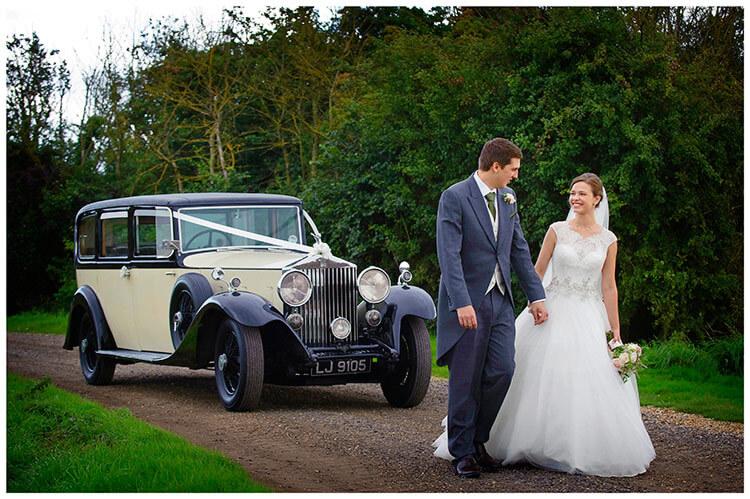 belfry hotel wedding bride groom smiling walking followed by car