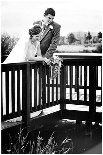 belfry hotel wedding bride groom standing on pontoon looking into lake