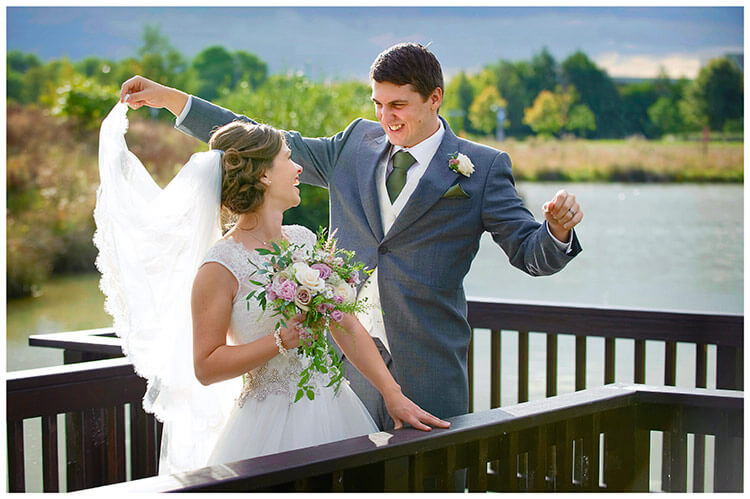 belfry hotel wedding groom holds brides veil as they laugh