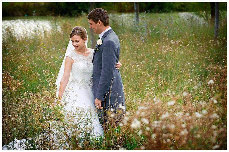 belfry hotel wedding bride groom hug standing in long grass
