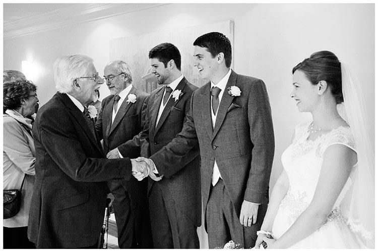 belfry hotel wedding groom shakes hand during receiving line
