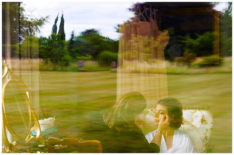 chippenham park summer wedding brides having make up applied, gardens reflected in window