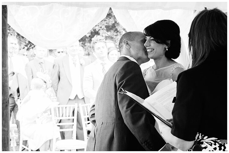 chippenham park summer wedding groom kisses bride on cheek at end of ceremony