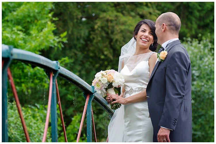 chippenham park summer wedding bride groom laughing on bridge