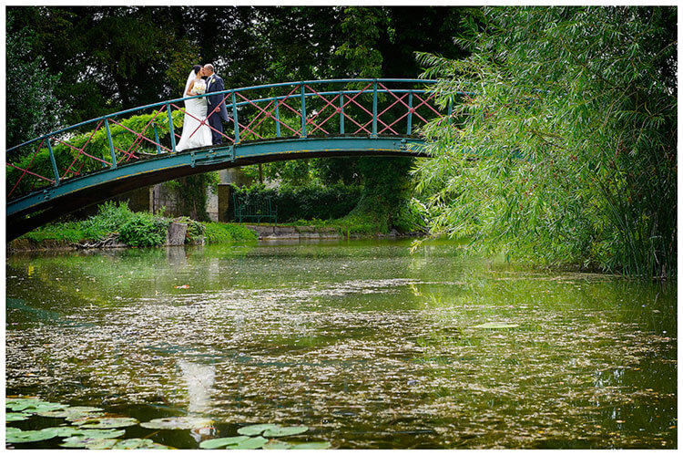 chippenham park summer wedding bride groom kiss on bridge over river