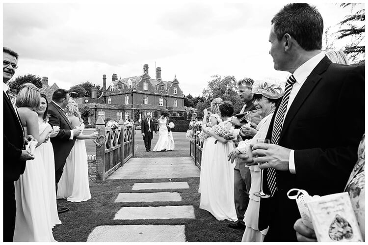 chippenham park summer wedding guests wait for bride groom so they can throw confetti