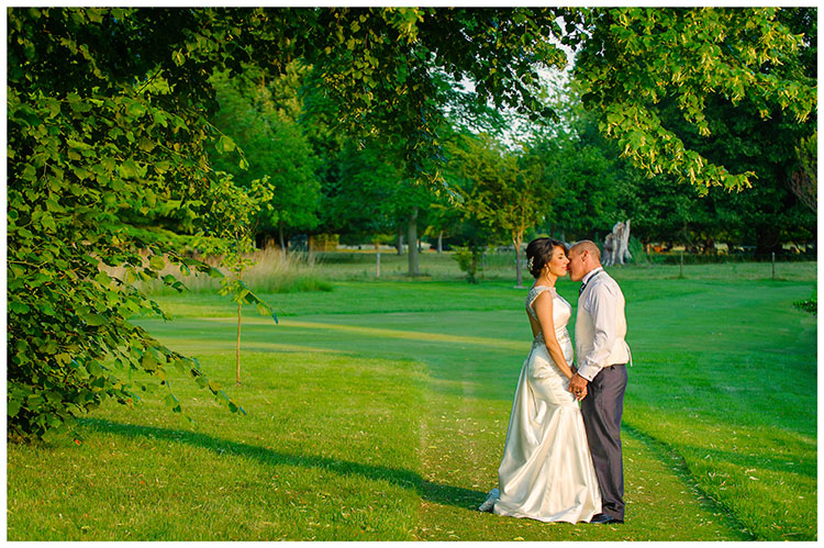 chippenham park summer wedding groom kisses bride