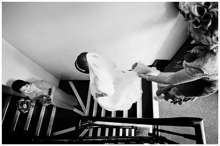 Emmanuel College wedding bridesmaid looks back at bride going down steps