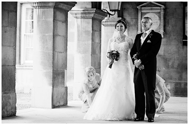 Emmanuel College wedding bridesmaids adjust brides dress