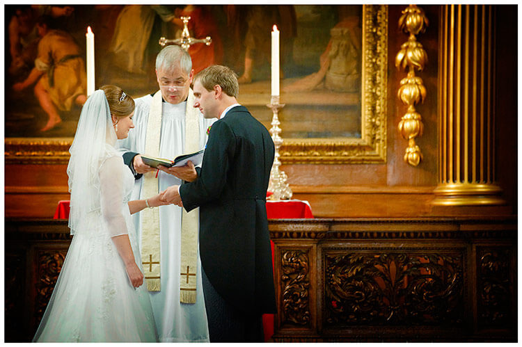 Emmanuel College wedding groom looks at bride as he places ring on brides finger