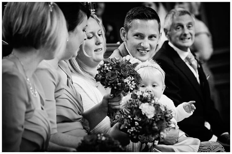 Emmanuel College wedding baby playing with bouquet