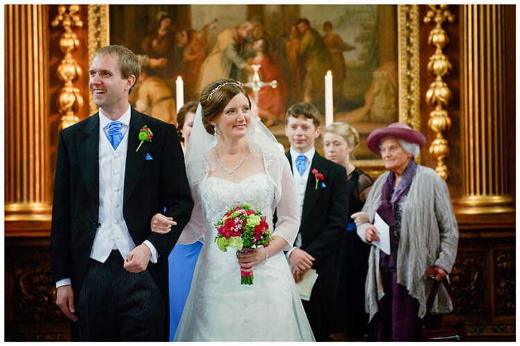 Emmanuel College wedding smiling bride groom arm in arm walking down aisle