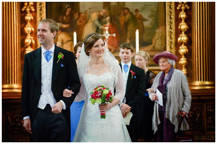 Emmanuel College wedding smiling bride groom arm in arm walking down aisle