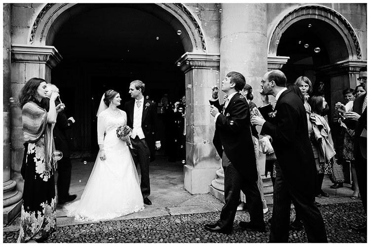 Emmanuel College wedding guest blowing bubbles at bride groom