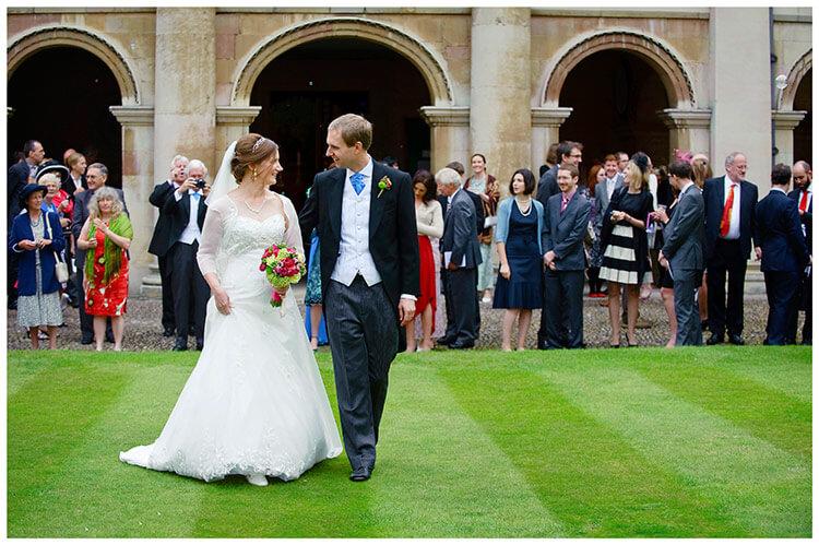 Emmanuel College wedding bride groom walking on grass guests in background