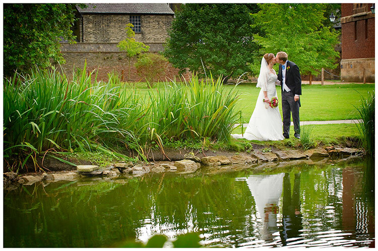 Emmanuel College wedding bride groom kiss near waters edge