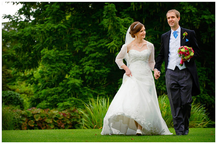 Emmanuel College wedding bride lifts dress groom holding bouquet as they hold hands and walk in gardens