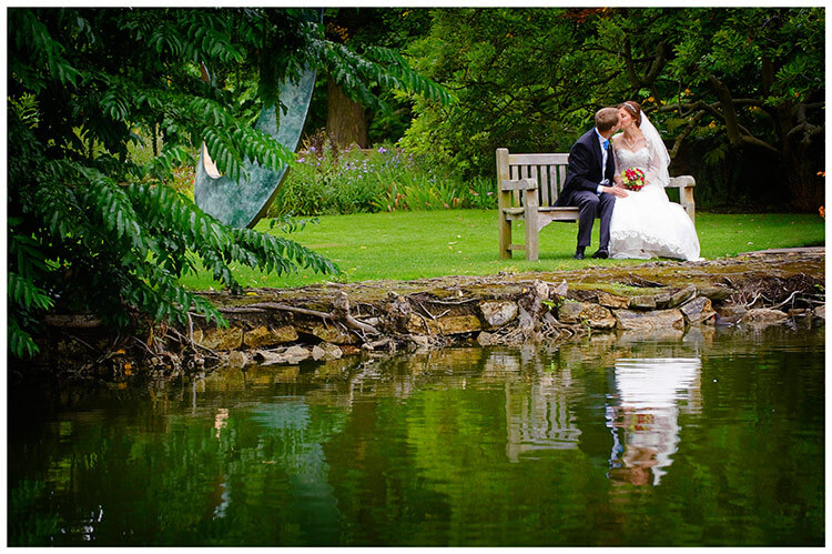 Emmanuel College wedding bride groom kiss sitting on bench