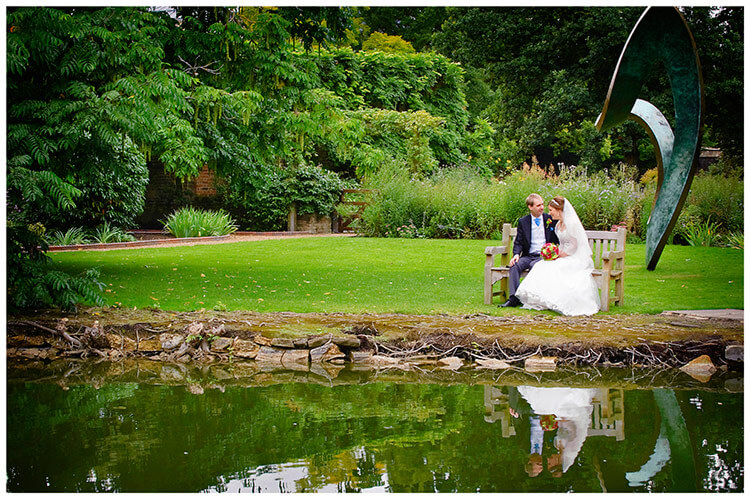 Emmanuel College wedding bride groom sitting on bench near waters edge statue in background