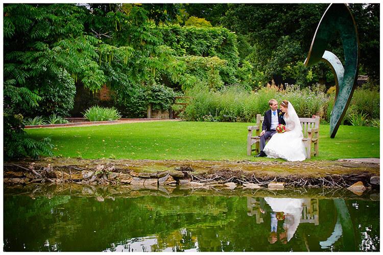 Emmanuel College wedding bride groom sitting on bench near waters edge statue in background